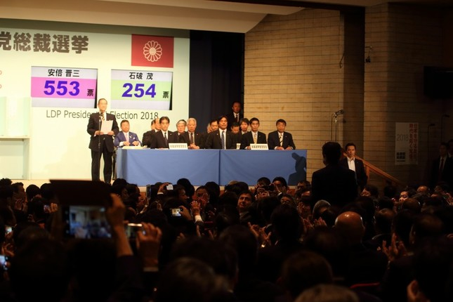 3選が決まり自席で立ち上がる安倍晋三首相(手前右)