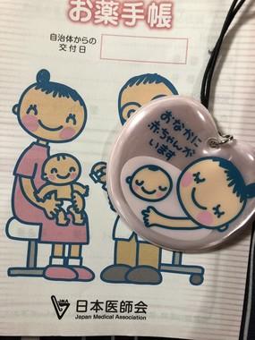 「母子のためのお薬手帳」の表紙と、マタニティマーク(写真提供:なみの(@syatikuzyanai)さん)