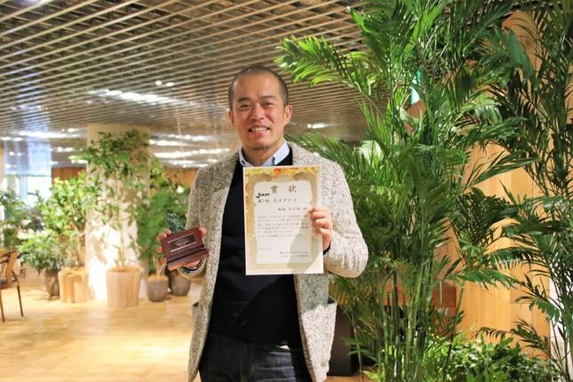 トロフィーと賞状を手にする田端信太郎さん