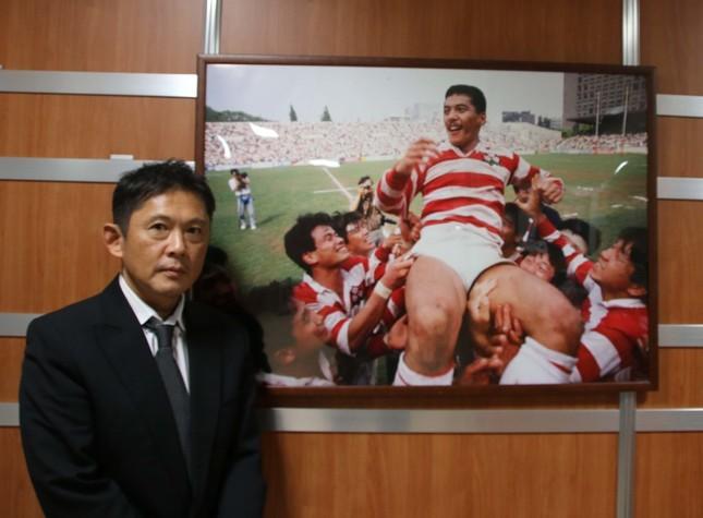 JRFUに飾られている平尾さんのパネル、その脇で平尾さんとの思い出を語る薮木氏
