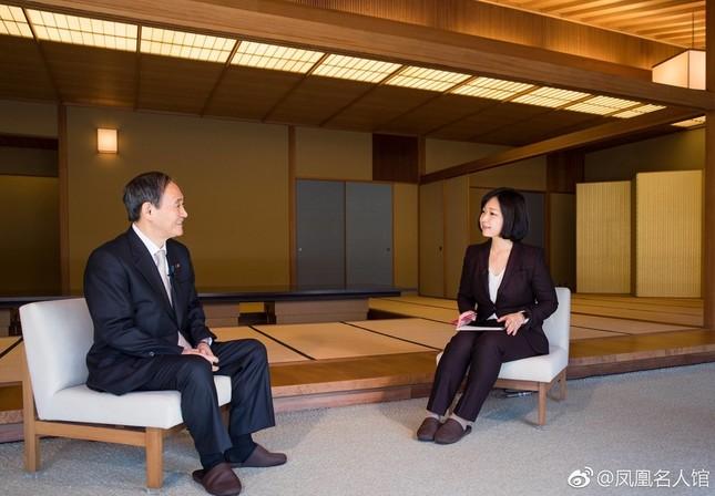 笑顔でインタビューに応じる菅義偉官房長官(左)。右側はフェニックステレビのリー・ミャオ東京支局長(写真はフェニックステレビオフィシャルサイトから)