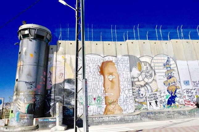実際の監視塔を抱きしめる、トランプ大統領のグラフィティが描かれている分離壁