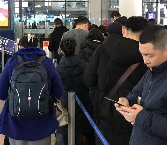 春節明け、上海駅切符売り場に並びながらスマホに見入る人たち