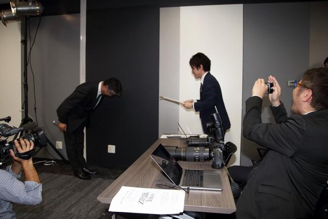 記者を「表彰」する西田真吾社長(左)