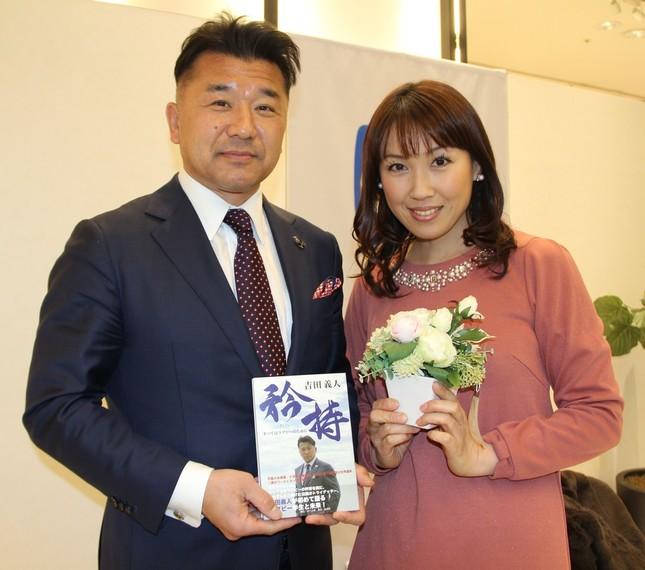 自身の著書「矜持」を手にする吉田義人氏と妻の亜里さん