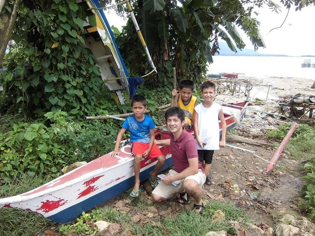 フィリピンの子どもたちと一緒に写る四倉禎一朗さん(写真提供:いしのまきNPOセンター)