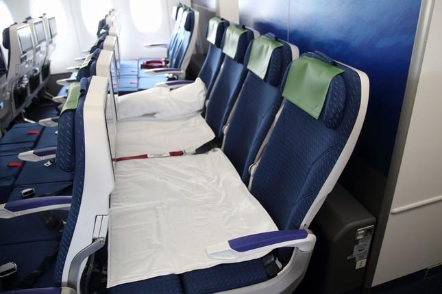 エコノミークラス後方に備えられたカウチシート。フットレストを水平に持ち上げて前の座席との間を埋めてベッド状にする