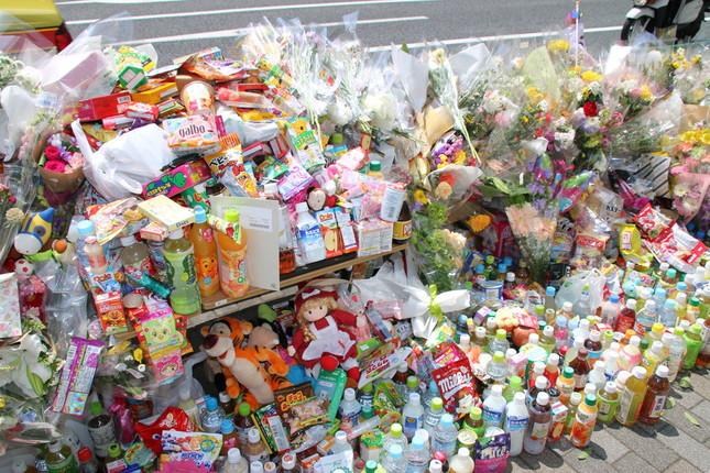 池袋の事故現場には、花束のほか菓子や飲み物なども続々と供えられた(2019年4月23日撮影)