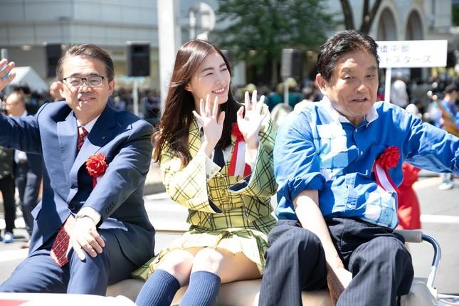 愛知県の大村秀章知事と名古屋市の河村たかし市長に挟まれながら沿道に手を振るSKE48の松井珠理奈さん(中央)(c)SKE