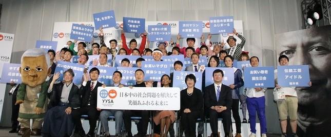 前列左から中村伊知哉さん、山里亮太さん、西川きよしさん、岡田昌治さん、スベンドリニ カクチさん、西原文乃さん、泉正隆さん。後段には全国住みます芸人の方々