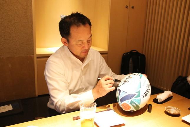 公式球にサインをする永友洋司さん