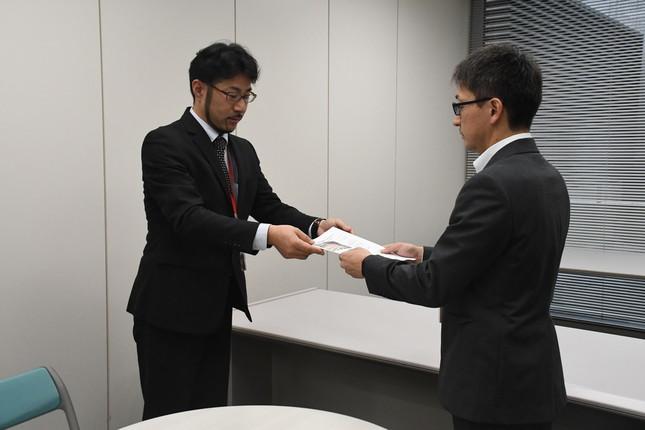 CD-ROMを手渡す畠山さん(左)