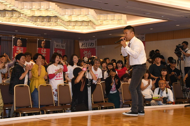 支持者らの前で述べる山本代表(右)