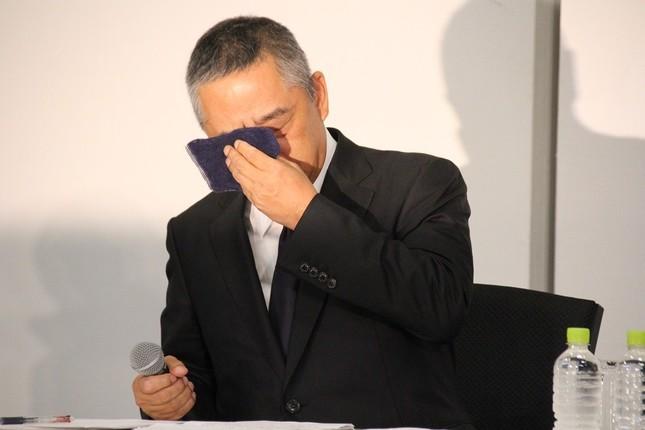 記者会見で涙をぬぐう岡本昭彦社長