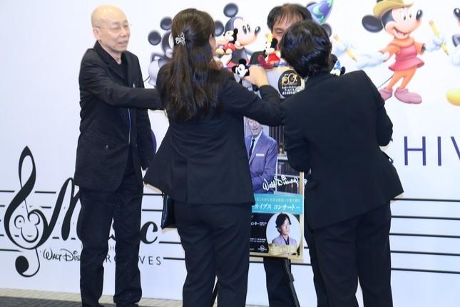 落下したミッキーマウスのぬいぐるみを拾い集めるスタッフと登壇者の島健さん(左)