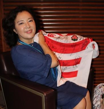 ラグビー日本代表の健闘を祈り、代表ジャージにサインする麻倉未稀さん