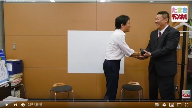 握手する玉木氏と立花氏