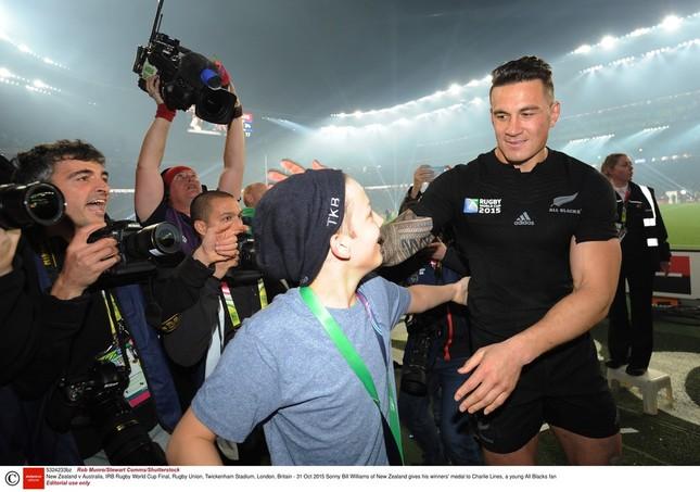 「2015イングランド大会」優勝後、ピッチに乱入してきた少年に金メダルをプレゼントしたオールブラックスのウィリアムズ選手(右) REX/アフロ