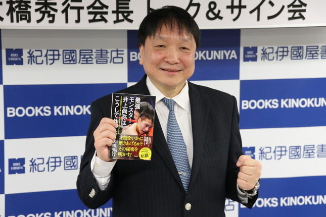 自著を持ち撮影に応じる大橋秀行会長