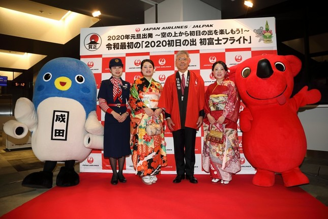 成田市の「うなりくん」(左端)や千葉県の「チーバくん」(右端)もフライトを見送った。中央は日本航空(JAL)の藤田直志(ただし)副社長
