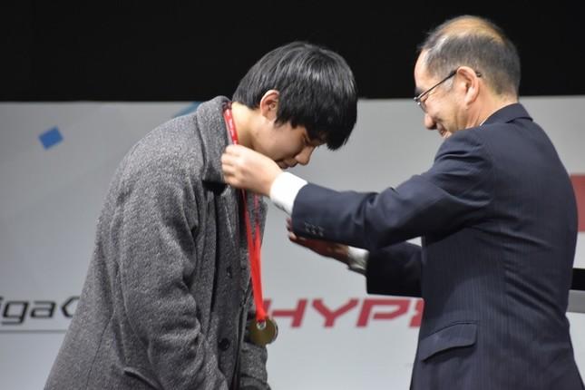 多羅尾光睦東京都副知事(右)からメダルを首にかけてもらう、やみえるぅ選手(左)