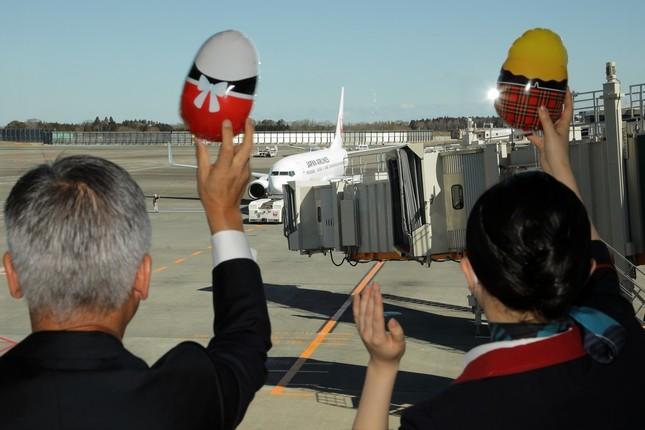 JALの藤田直志(ただし)副社長(写真左)らは、マトリョーシカ風の風船を手に初便を見送った