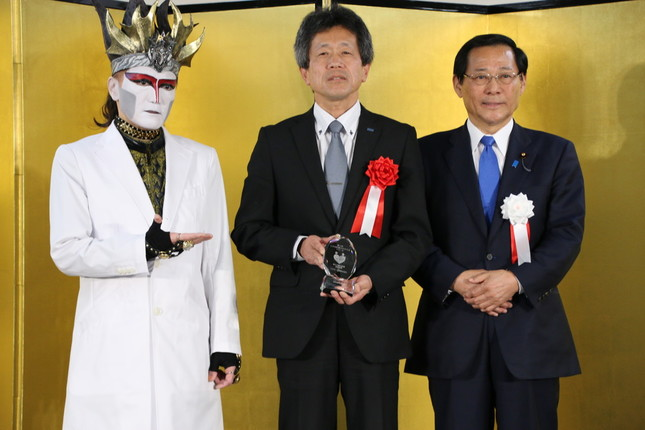 (左から)デーモン閣下、厚生労働大臣賞受賞のブラザー工業、小島政務官