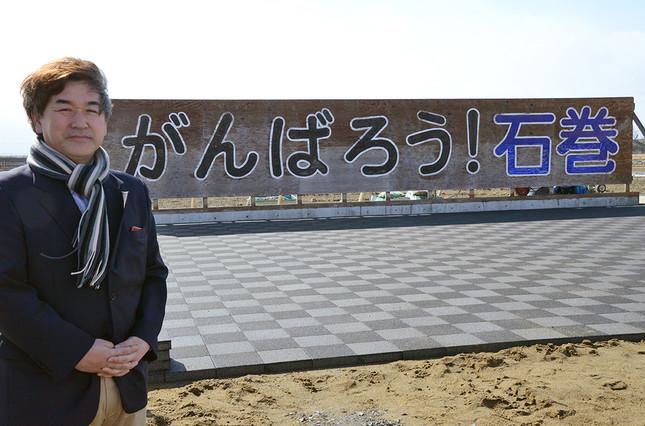 黒澤健一さん。「がんばろう!石巻」の看板前で