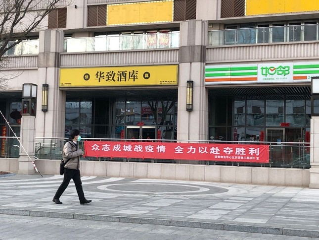 北京市内に張られた新型コロナウイルスと戦うスローガン(下の赤い横断幕)。北京では多くの企業が仕事を始めたが、まだ市内を歩く人は少ない(2020年3月11日)