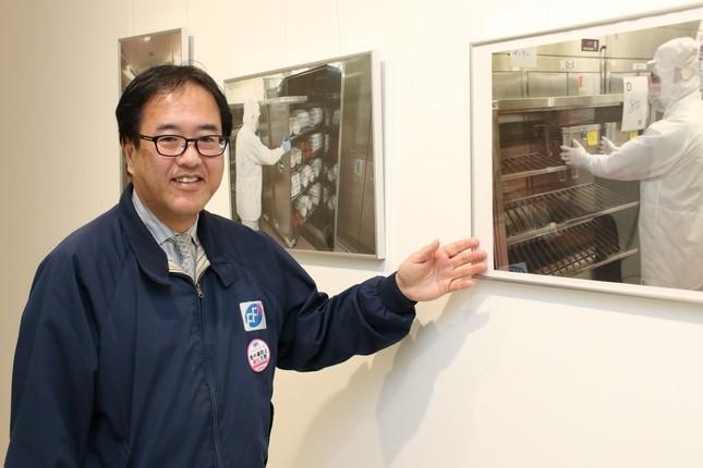 給食センター内の作業を写真で説明する渋谷昌俊社長