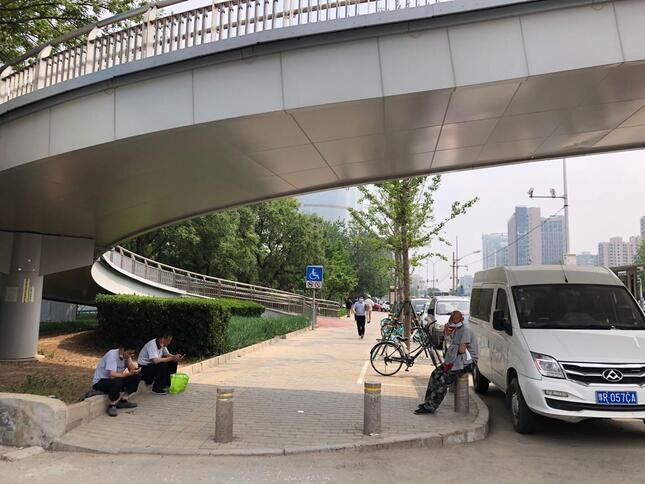 北京市内の「首都体育館」近くの横断歩橋橋の下で涼を取る出稼ぎ労働者たち。コロナショックの前は多くの労働者が群がっていたが、現在は人影もまばらだ(2020年5月6日、筆者撮影)