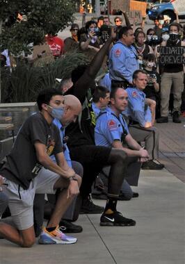 黒人死亡の抗議デモで、デモに共感を示してひざまずく警察官(2020年6月2日、ノースカロライナ州ローリーで James Willamorさん撮影、Wikimedia Commonsよ り)