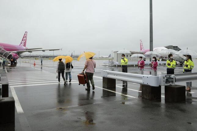 この日の関西空港は雨。客室乗務員らが傘を持って乗客を見送った