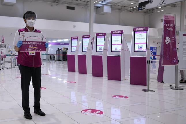 関西空港のチェックイン機では、係員が間隔を開けて並ぶように呼びかけた