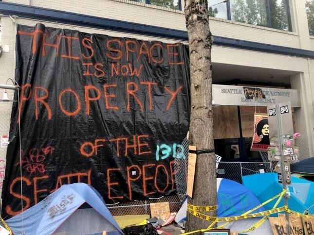 占拠されたシアトル警察東管区の建物出入口にかけられた防水シート。シートには「この場所は今、シアトル市民の所有物だ」と書かれている(2020年6月23日、ワシントン州シアトルで Benjamin Morawekさん撮影、Wikimedia Commonsより)