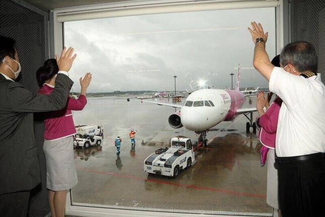 ピーチの森健明(もり・たけあき)代表取締役CEO(写真左)らが、この日運航を再開した便を見送った。15時過ぎに乗客63人を乗せて鹿児島に向けて出発した