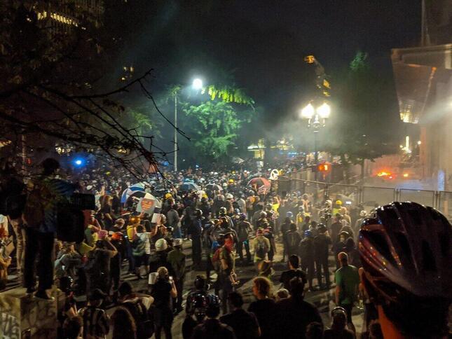 抗議活動が続くポートランド。群衆の奥では、小さいながら炎が燃えている。7月22日、Tedderさん撮影。Wikimedia Commonsより。