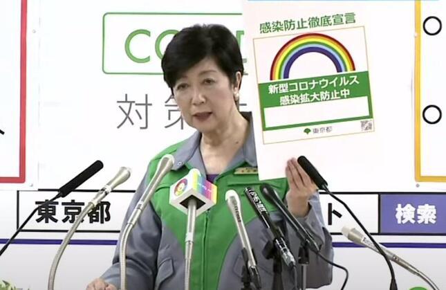 ステッカーを掲げる小池百合子都知事(都のユーチューブチャンネル7月31日の動画から)