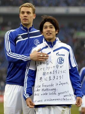 東日本大震災でメッセージを贈る内田篤人選手(右)とマヌエル・ノイアー選手(写真:AP/アフロ、2011年3月12日撮影)