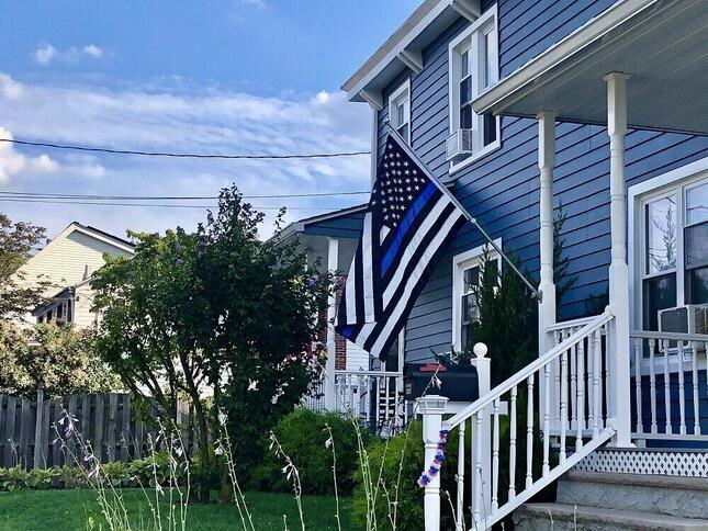 警察への支持や殉職した警官への追悼を表す「Thin Blue Line Flag」。トランプ支持者の多い地域ではよく、家の前にこの旗が掲げられている(2020年8月、ニューヨーク市スタテンアイランドで著者撮影)