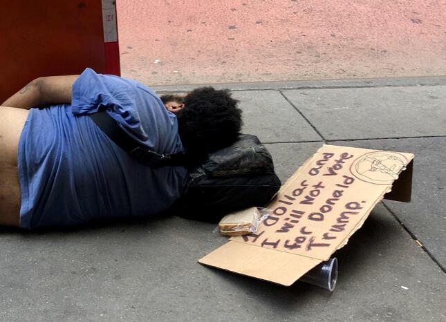 ニューヨークのブロードウエイ劇場街で横たわるホームレス。脇の段ボールには大統領 選にからめた「サイン」があった(2020年8月、筆者撮影)