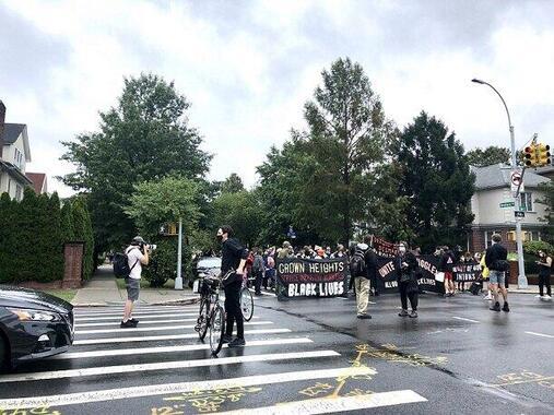 ニューヨークで社会主義を唱えるデモ行進が通りかかる交差点で自転車を止め、デモ隊を誘導する人たち(2020年8月、筆者撮影)