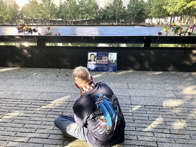 同時多発テロにより当時26歳で亡くなった知人男性の遺影を追悼碑の前に掲げ、見つめるコネティカット州の男性(2020年9月、筆者撮影)