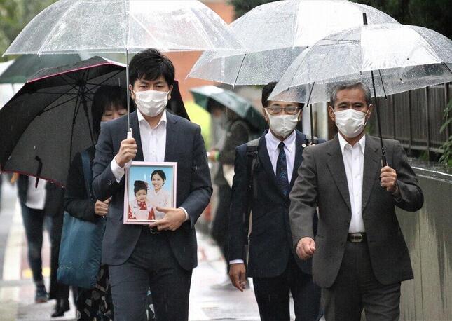 初公判前、真菜さんと莉子ちゃんの遺影を持つ遺族の松永拓也さん(手前左)