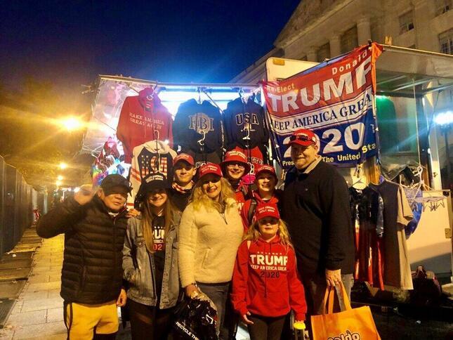 ワシントンでのトランプ支持者の集会にサウスカロライナ州からやってきた家族。後ろはトランプグッズなどを売る屋台(2020年11月、筆者撮影)