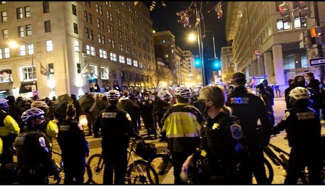 ワシントンで行動を共にしたプラウド・ボーイズから見た警官隊の列。反対側で黒い傘を差しているのが対立するアンティファ(2020年11月14日、筆者撮影)