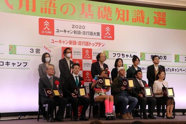 2020年の流行語大賞の受賞者(前列)と選考委員(後列)による記念撮影の中、かじりつく素振りを見せるフワちゃん(前列中央)