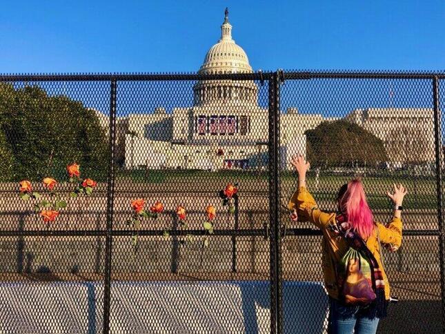 ワシントンにある議事堂前のフェンスに供えられたバラ。その傍らでフェンスにしがみつき、嘆き悲しむ女性(2021年1月、筆者撮影)