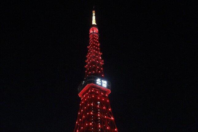 赤くライトアップされた東京タワー。展望台メインデッキの窓にはLEDで「希望」の2文字が投影された