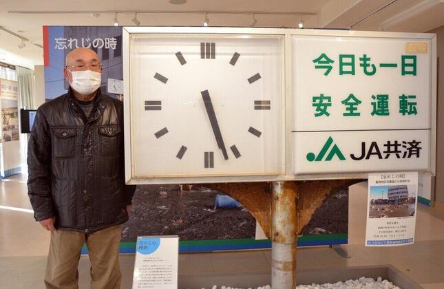 仲條富夫さん。旭市に津波の「第3波」が到来した際に止まったJAの時計の横に立つ